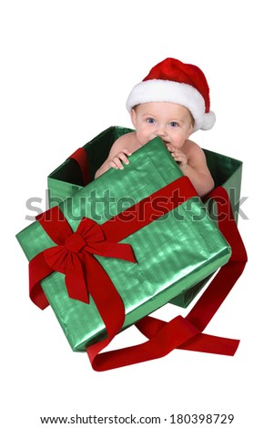 Baby wearing santa hat inside green and red Christmas present box on white  - stock photo
