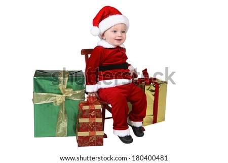 Baby wearing santa outfit sitting in chair surrounded by presents