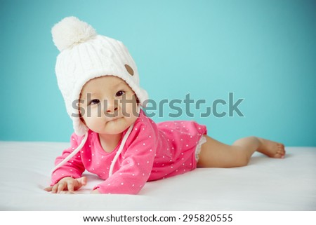 Baby wearing white knitted beanie in front of blue background - stock photo