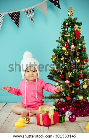 Baby wearing white knitted beanie in front of blue background and Decorating Christmas tree on green background - stock photo