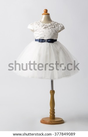 Baby white dress on a mannequin, light gray background