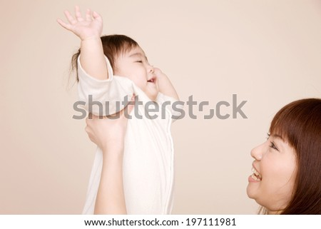 Baby Who Is Happy While Being Lifted By Mother - stock photo