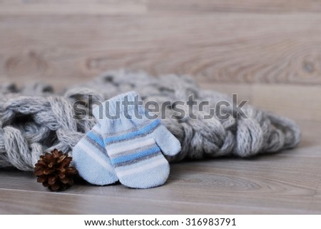 Baby winter gloves, cone and knitted wool scarf on wooden board. Winter children background. - stock photo