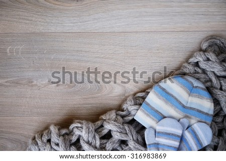 Baby winter gloves, hat and knitted wool scarf on wooden board with copy space for text. Winter children background. - stock photo