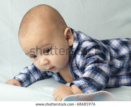 baby with a blue shirt resting on a blue towel - stock photo