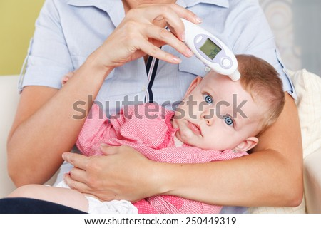 Baby with a digital thermometer - stock photo