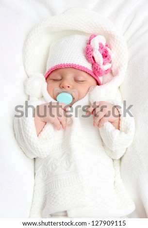 Baby with a knitted white hat baby on back - stock photo