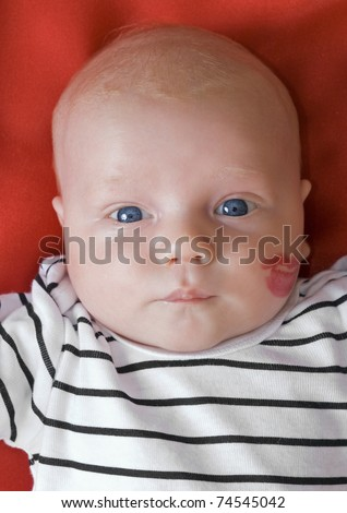 Baby with a lipstick kiss on cheek - stock photo