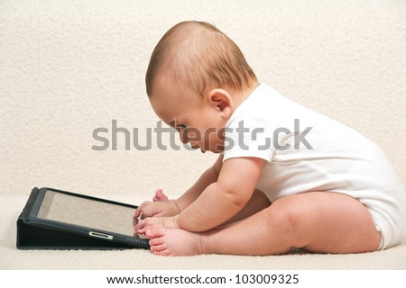 Baby with a small computer - stock photo