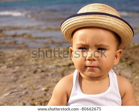 baby with a straw hat in the beach - stock photo
