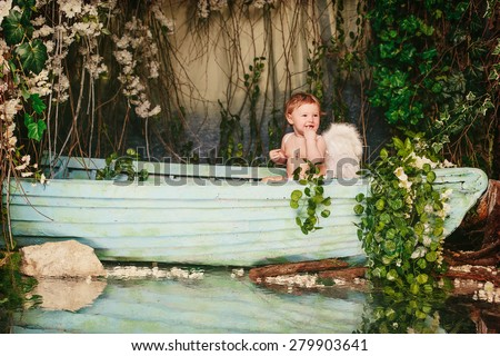 Baby with angel wings in a boat with flowers  background - stock photo