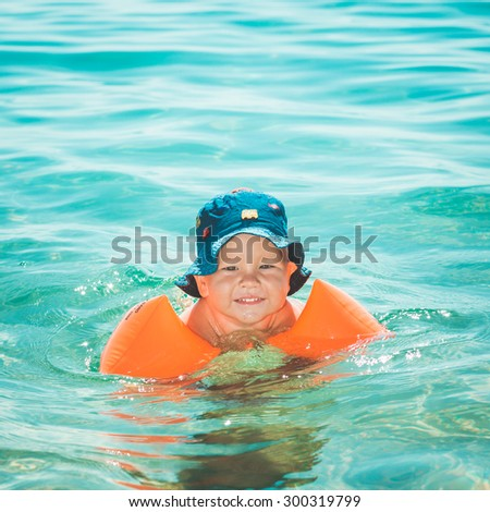 Baby with armbands in a sea - stock photo