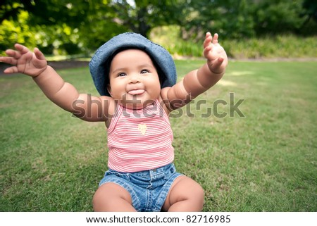 baby with arms in the air and blowing raspberries - stock photo