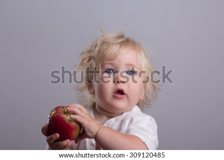 baby with blond long hair holds a red apple