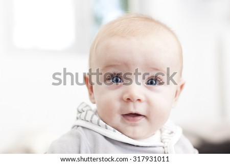 Baby with blue eyes looking to the camera and smiling - stock photo