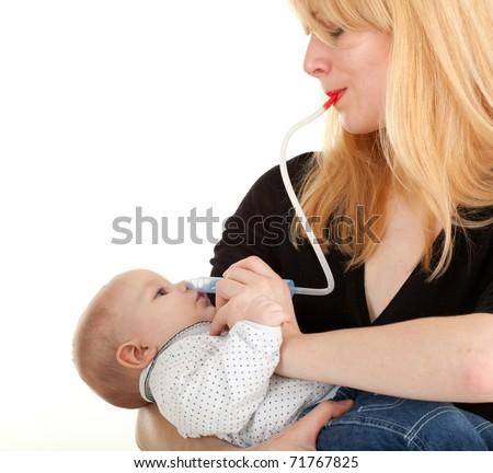 baby with cattarrh - mother using child's nasal aspirator - stock photo