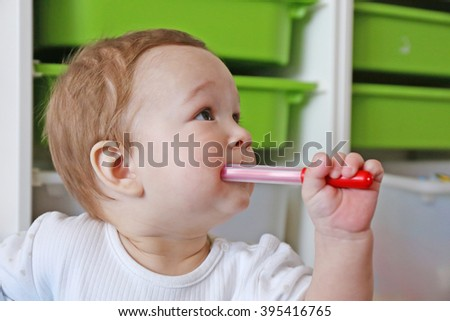 Baby with colored markers in a room - stock photo