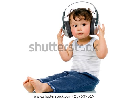 Baby with headphones, isolated on a white background. - stock photo
