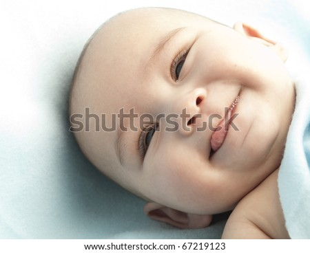 baby with her tongue out on a cotton blanket - stock photo