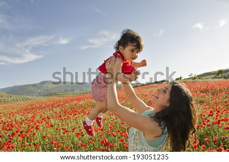 Baby with his mom enjoying a field day outdoors - stock photo
