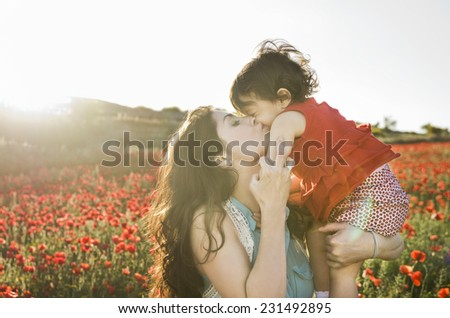 baby with his mother enjoying a field day outdoors, kissed in sunset back light - stock photo