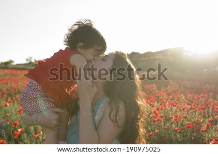 baby with his mother enjoying a field day outdoors, kissed in sunset backlight - stock photo