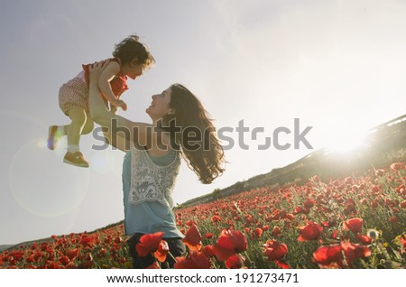 baby with his mother enjoying a field day outdoors. Sun flare in burned sky. - stock photo