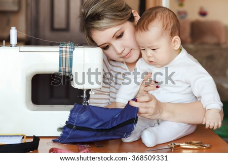 Baby with his mother seamstress, home, natural light, infant curiously looking to sewing machine. Child care and work at home.  - stock photo