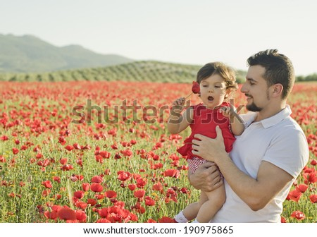 baby with his parent enjoying a field day outdoors - stock photo