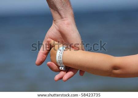 Baby with info band on his wrist with name and his mother's and father's  phone number. - stock photo