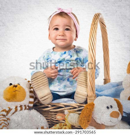 Baby with many teddies over grey background