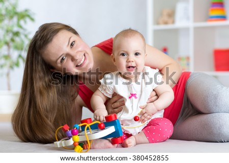 Baby with mom. Mother and daughter indoor. Little girl and woman play together. - stock photo