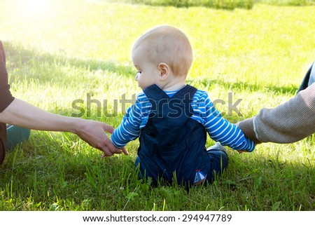 Baby with mother and father holding hands on the nature - stock photo