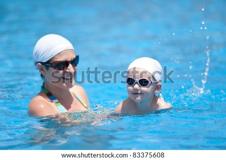 Baby with mother is swimming in pool