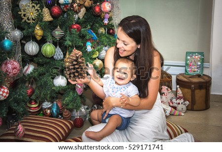 baby with mum sitting near Christmas tree in the house