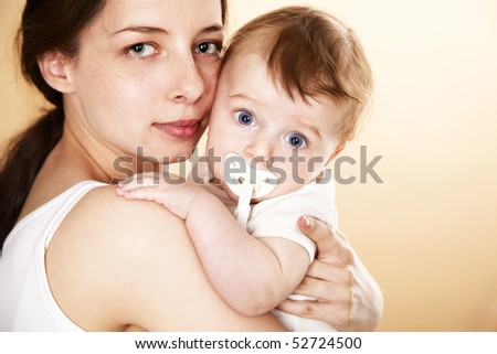 baby with pacifier in mother arm; closeup faces - stock photo