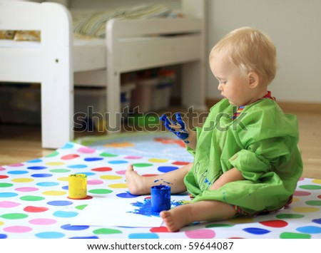Baby with paint on hands - stock photo
