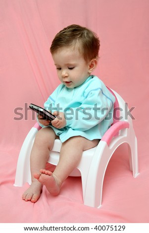 baby with pocket PC sitting on chamber-pot - stock photo