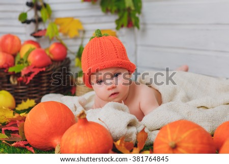 Baby with pumpkin and apples. Autumn