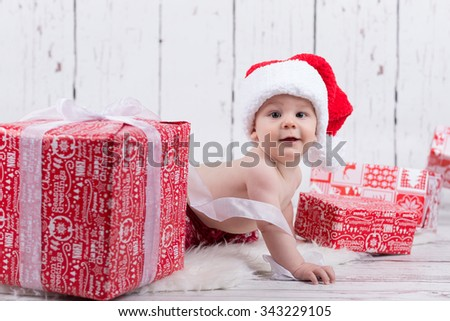 baby with red cap with ribbon behind the gift
