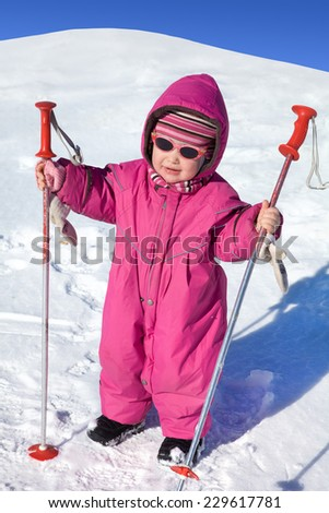 baby with ski poles in the snow making moves on winter resort - stock photo