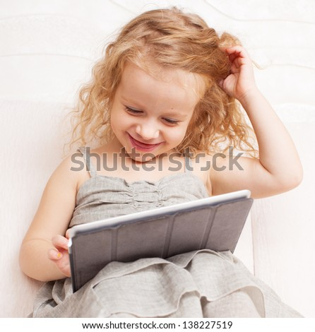 Baby with tablet computer. Little child playing at home on sofa - stock photo