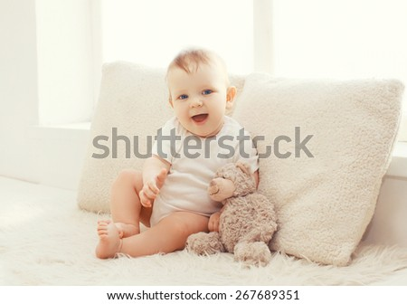 Baby with teddy bear at home in white room near window