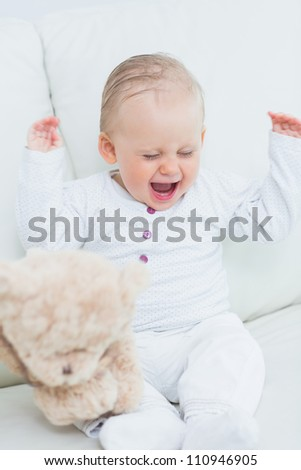 Baby with teddy bear in living room - stock photo
