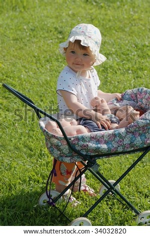 Baby with toy carriage - stock photo