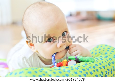 baby with toy in mouth - stock photo