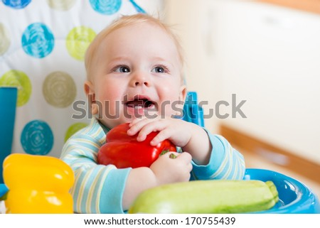 baby with vegetables sitting in chair on kitchen - stock photo