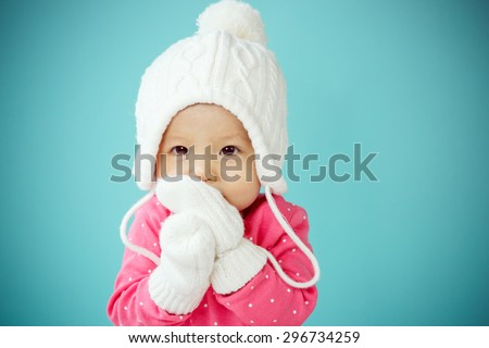 Baby with white poodle hat and knitted mittens - stock photo