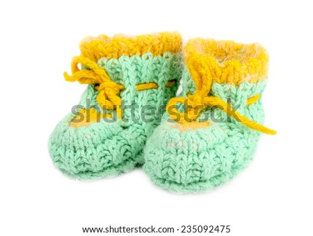 Baby woolen booties, knitted of green and yellow thread - stock photo