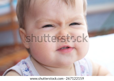 Baby wrinkling her nose expressing happy emotions - stock photo